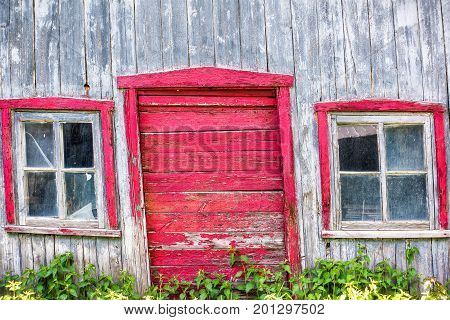 Red Painted Old Vintage Shed With Yellow Dandelion Flowers In Summer Landscape Field In Countryside