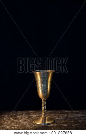 Vintage copper goblet for wine on wooden and black background