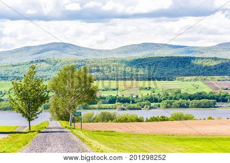 Ile D'Orleans Canada - June 1 2017: Landscape with plowed field in summer and trail path road with private sign