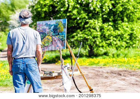 Ile D'Orleans Canada - June 1 2017: Artist man with painting on easel by countryside landscape in summer and trail path road with flowers