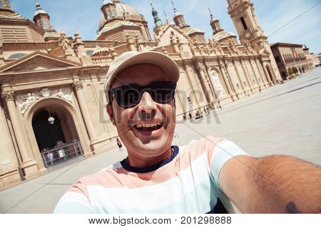 closeup of a young caucasian man smiling to the camera while is taking a self-portrait in front of the Cathedral-Basilica of Our Lady of the Pillar in Zaragoza, Spain