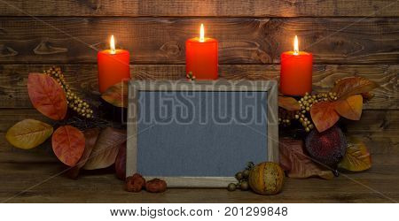 Burning autumn candles with a blank chalkboard on a wood background