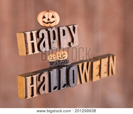 Wood letters spelling happy halloween floating on an orange background