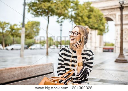Lifestyle portrait of a young stylish business woman talking with phone outdoors near the famous triumphal arch in Paris