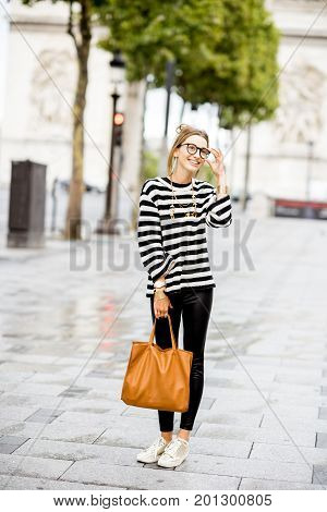 Lifestyle portrait of a young stylish business woman in striped sweater outdoors near the famous triumphal arch in Paris