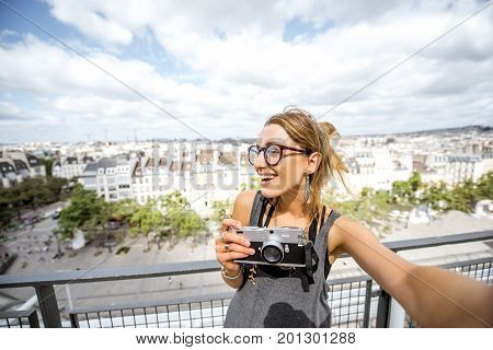Young woman making selfie photo on the Paris skyline background