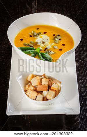Pumpkin soup with cream and pumpkin seeds on dark wooden background. Copy space.