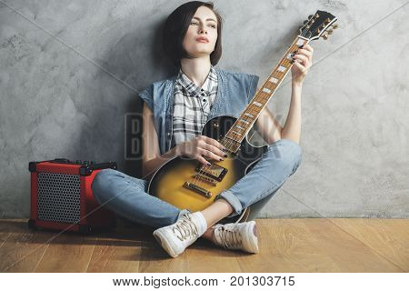 Attractive woman with electric sunburst guitar and amplifier sitting in studio room with wooden floor and concrete wall. Musician concert hobby leisure rehearsal concept