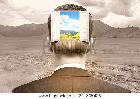 Back view of businessman with abstract open door and landscape view in head on desert background. Opportunity concept
