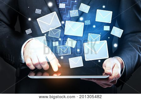 Close up of businessman hands using tablet with digital e-mail hologram. Email marketing concept