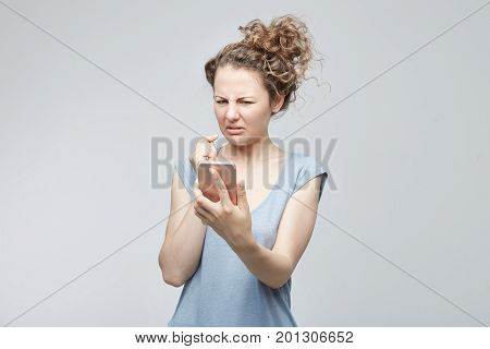 Closeup portrait anxious or shocked young freelancer woman looking at phone seeing bad news or photos with disgusting emotion on her face isolated grey background. Human emotion reaction expression.
