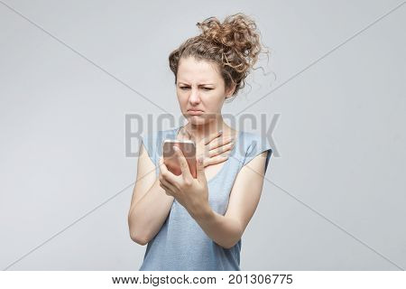 Studio shot of anxious or shocked young freelancer lady looking at phone seeing sad news or photos with disgusting emotion on her face isolated grey background. Human emotion reaction expression.