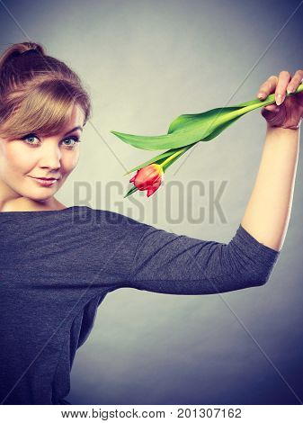 Spring time. Craziness and fun concept. Playful happy girl playing with flower. Joyful smiling funny positive female person making crazy figures with tulip.