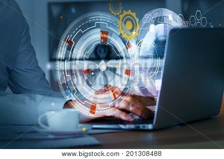 Side view of businessman hands using laptop with business screen hologram placed on office desktop with coffee cup. Accounting concept. Double exposure