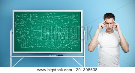 Pensive man standing next to chalkboard with mathematical formulas on blue wall background. Exam concept. 3D Rendering