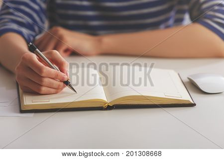 Young woman in striped shirt writing in hardcover copybook placed on light office workplace desktop with items. Paperwork concept