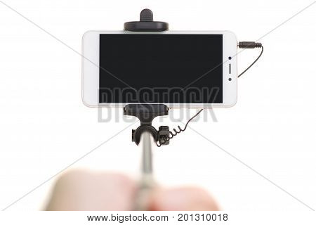 Smartphone and selfie stick in hand on white background isolation