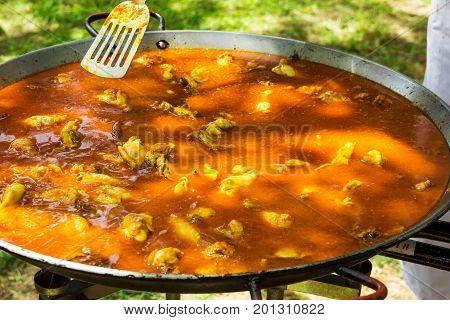 Process of cooking Spanish paella or jambalaya in large flat frying pan. Metal turner tossing ingredients in tomato sauce. Outdoors picnic.
