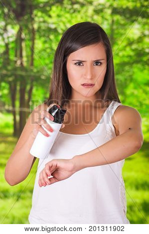 Beautiful young woman using a spay over the insect to kill it, in a blurred background.