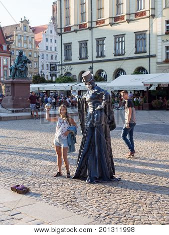 WROCLAW POLAND - AUGUST 14 2017: Mime Artist Street Performer With Tourist Girl At Rynek Market Square In Wroclaw