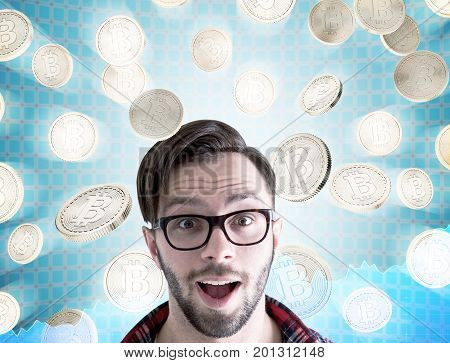 Close up of an astonished young man wearing glasses and a checkered shirt. He is standing under a bitcoin rain against a futuristic background. Toned image double exposure