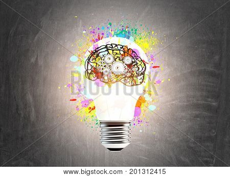 Large glowing light bulb sketch is drawn on a chalkboard There is a small colorful brain icon with cogs on it. Toned image