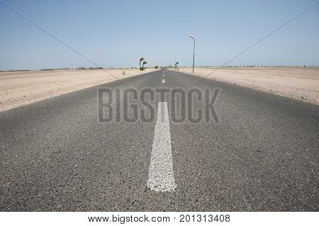 Long straight desert road in remote arid landscape going to infinity vanishing point