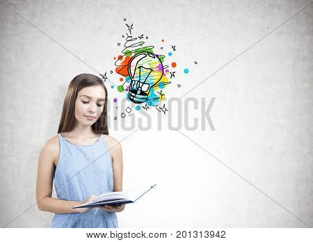 Portrait of a teen girl wearing a blue dress and holding an open book. She is reading while standing near a concrete wall with a small and colorful light bulb sketch. Mock up