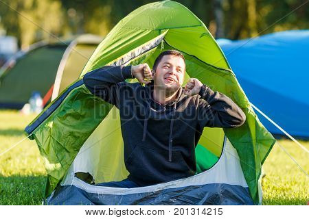 The man woke up, sat down and stretched himself in the tent. Morning awakening in the camp.