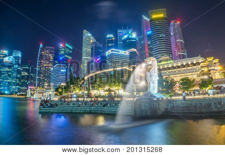 Singapore, Singapore - July 22, 2017: Tourists beside the Merlion statue fountain, iconic symbol of Singapore, overlooking the Marina Bay waterfront, the Esplanade Theatres, luxury hotels