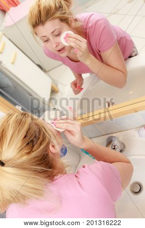 Woman Using Cotton Pad To Remove Make Up