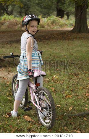Little girl riding bike wearing helmet.
