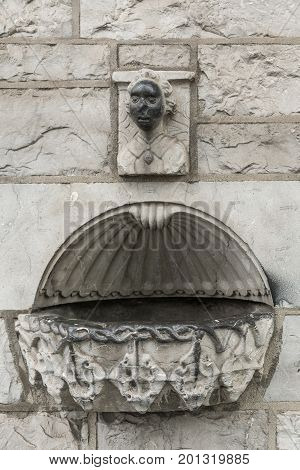 Galway Ireland - August 3 2017: Old gray granite holy water font built in outside wall of Saint Francis Abbey Church. Small blackened human face statue above.