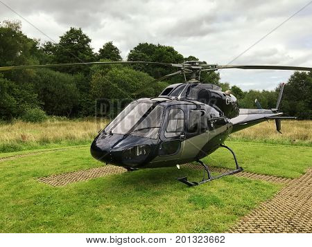Front side view of a black squirrel helicopter that landed on the H helicopter landing spot. With grass and trees in the background on a cloudy day.