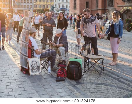 WROCLAW POLAND - AUGUST 14 2017: Street Painter Painting A Portrait of A Tourist At Rynek Market Square In Wroclaw