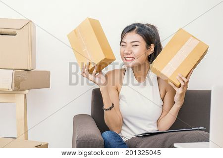 Start up small business entrepreneur or freelance woman holding boxes working at home concept Young Asian small business owner at home office on line marketing packaging and delivery