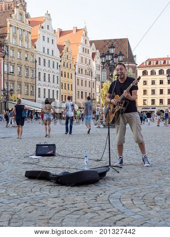 WROCLAW POLAND - AUGUST 15 2017: Street Musician With Guitar At Rynek Market Square In Wroclaw
