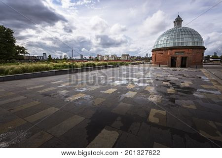 Wide angle shot from the Greenwich Foot Tunnel South entrance with reflection on a wet flor with a cloudy sky and building in the background. Greenwich London.