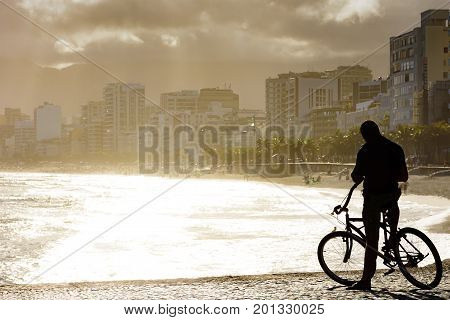 Cyclist in front of the sea during late afternoon at Arpoador beach in Ipanema Rio de Janeiro