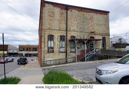 CADILLAC, MICHIGAN / UNITED STATES - MAY 31, 2017:  An historic brick building, at the corner of Beech and Mitchell Streets, houses the Cadillac Masonic Center and various businesses.