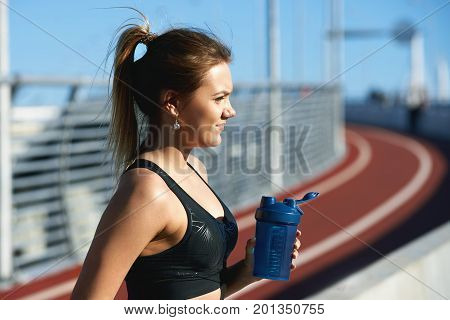 Thirst and dehydration concept. Profile shot of charming thirsty young woman runner or jogger in sports outfit having rest after morning run at outdoor stadium drinking water out of plastic bottle