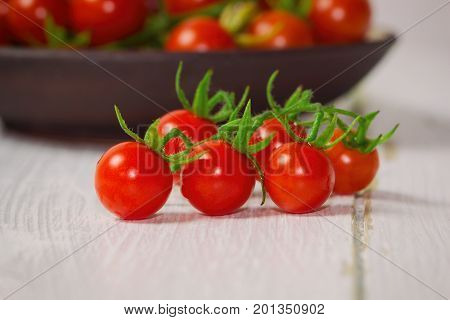 Fresh cherry tomato on white wood table. Close up lovely cherry tomato for background or wallpaper. Prepare fresh cherry tomato for home cooking look so delicious. Side view concept with copy space. Cherry tomato for fresh vegetable concept