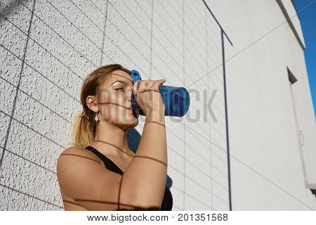 Sports active lifestyle and dehydration concept. Outdoor shot of attractive tanned young woman runner with athletic body drinking water from plastic bottle feeling thirsty after running workout