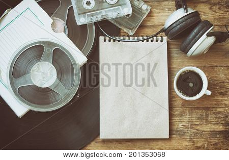 Retro music background vinyl records film reel audio cassettes headphones cup of coffee and notebook