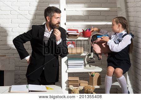 Girl And Man Near Bookshelf With School Supplies