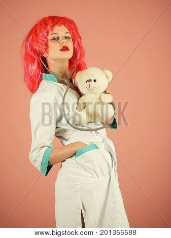 Woman wearing medical uniform and red wig. Nurse on pink background. Health care and cure concept. Doctor and patient. Girl examining teddy bear toy with stethoscope.