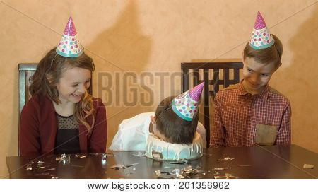 carefree children at a birthday party. boy dunked face in the birthday cake. family celebration concept