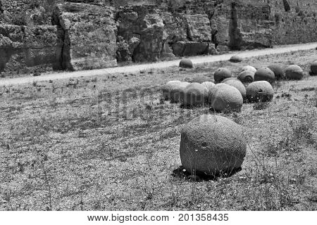 ancient stone spheres or kernels are located chaotically and abstractly on the old dry soil and one sphere in the foreground