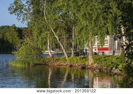 HEINOLA, FINLAND ON JULY 01. View of caravans on July 01, 2017, in Heinola Camping, Finland. Lake and trees this side, evening sunshine. Speedboat in the background. Editorial use.
