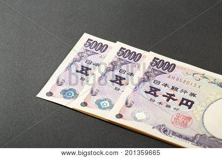 Three Japanese bank note 5000 yen on black background